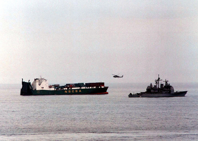 The guided missile cruiser USS San Jacinto (CG 56) (right) and an SH-60B Seahawk helicopter from the Nightdippers of Anti-Submarine Squadron Five (HS-5) come to the aid of the Saudi container ship Saudi Hofuf in the Gulf of Oman, March 21, 1996. The Saudi Hofuf was rapidly taking on water and in danger of sinking due to a ruptured seal in the main spaces. The San Jacinto sent over a party of damage control men and engineers who aided in efforts to keep the ship afloat. Navy helicopters aided in evacuating non-essential personnel from the stricken vessel. USS San Jacinto is part of the aircraft carrier USS George Washington (CVN 73) battle group