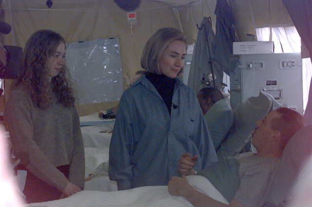 First Lady Hillary Rodham Clinton and daughter Chelsea Clinton visit with a soldier hospitalized in the 212th MASH (Mobile Army Surgical Hospital) located at Camp Bedrock, Bosnia-Herzegovina. The hospital wards were visited briefly by the two during a visit to the Tuzla area base camps during Operation Joint Endeavor