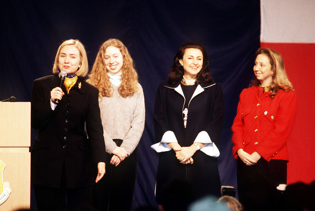 First Lady, Hillary Rodham Clinton, speaks to the men and women of Aviano Air Base, Italy. Standing behind her is her daughter, Chelsea Clinton, along with the First Lady of Italy, Mrs. Donatella Zingone Dini, and her daughter. Mrs. Clinton is on a 10-day tour that includes stops in Germany, Bosnia and Herzegovina, Italy, Greece and Turkey