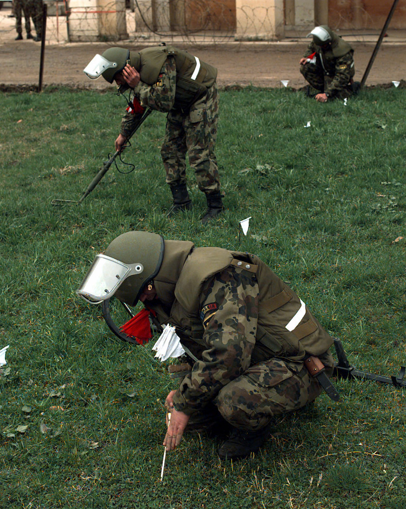 Romanian Army Explosives Ordnance Disposal soldiers probe and sweep for mines or unexploded ordnance during Operation JOINT ENDEAVOR. The soldiers mission is to clear the Implementation Force compound, a plaza between the Hotel Serbia and the Hotel Herzegovina in the Sarajevo suburb of Ilidza, Bosnia and Herzegovina