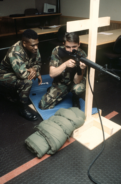 SENIOR AIRMAN Lloyd Wood, 55th Security Police Squadron instructs SENIOR AIRMAN Delanie Stafford as he fires from the kneeling position at the target screen of the Fire Arms Training System at Offutt AFB, Neb