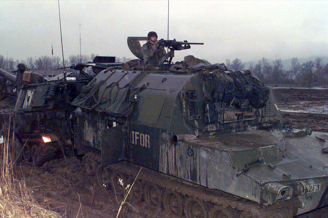 "From front to rear an M-992 ""Cut V"" Ammunition Carrier and an M-109 155 mm Self Propelled Howitzer stand back to back while a Section Evaluation is conducted by members of the C Battery, 23rd Field Artillery, 2nd Battalion from Kirchgon, Germany at Camp Vicaisson, Bosnia-Herzegovina during Operation Joint Endeavor"