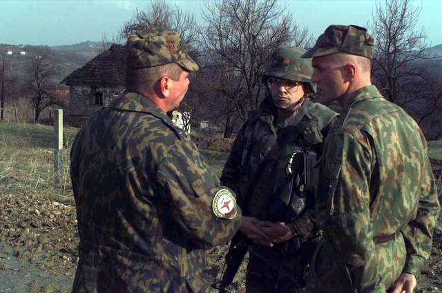 Russian and American soldiers work together at check point 36A (34TCQ 215514) located in the Russian Brigade Area of Operation, Bosnia-Herzegovina during Operation Joint Endeavor. They are discussing a mine strike after a Russian soldier stepped on an anti-personnel