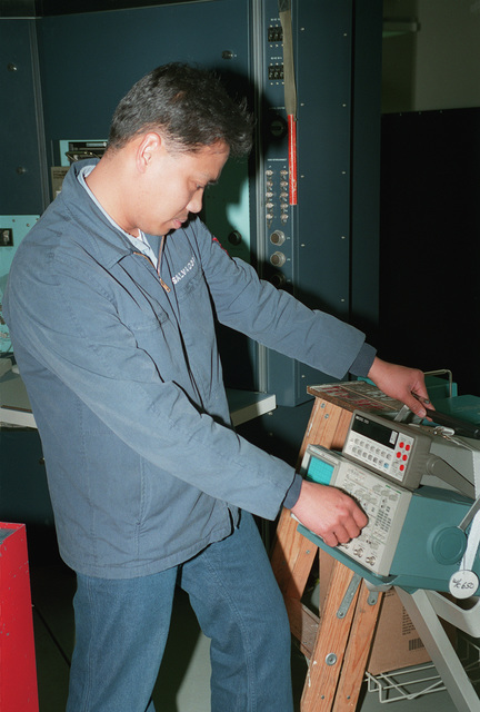 Aviation Structural Mechanic First Class (AMS1) Joel Salvador is inspecting an oscilloscope at the Aircraft Intermediate Maintenance Department (AMID) at Naval Air Facility Unit 5048