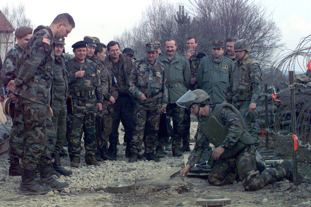 SGT Alcantar Francisco of A Company, 40th Engineer Battalion, kneels on the ground and demonstrates to members of the Joint Military Commission (JMC)how to probe for mines during a meeting at 1-4 CAV JMC Site (CQ347027), Bosnia-Herzegovina during Operation Joint Endeavor