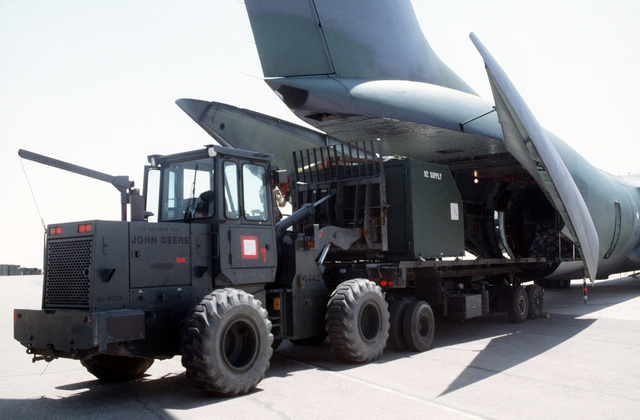Personnel from the 621st Aerial Port Squadron out of McGuire Air Force Base, New Jersey, unload cargo from a C-141B Starlifter using a John Deere forklift. The supplies will be used in support of Air Power Expeditionary Force exercise with the Royal Jordanian Air Force