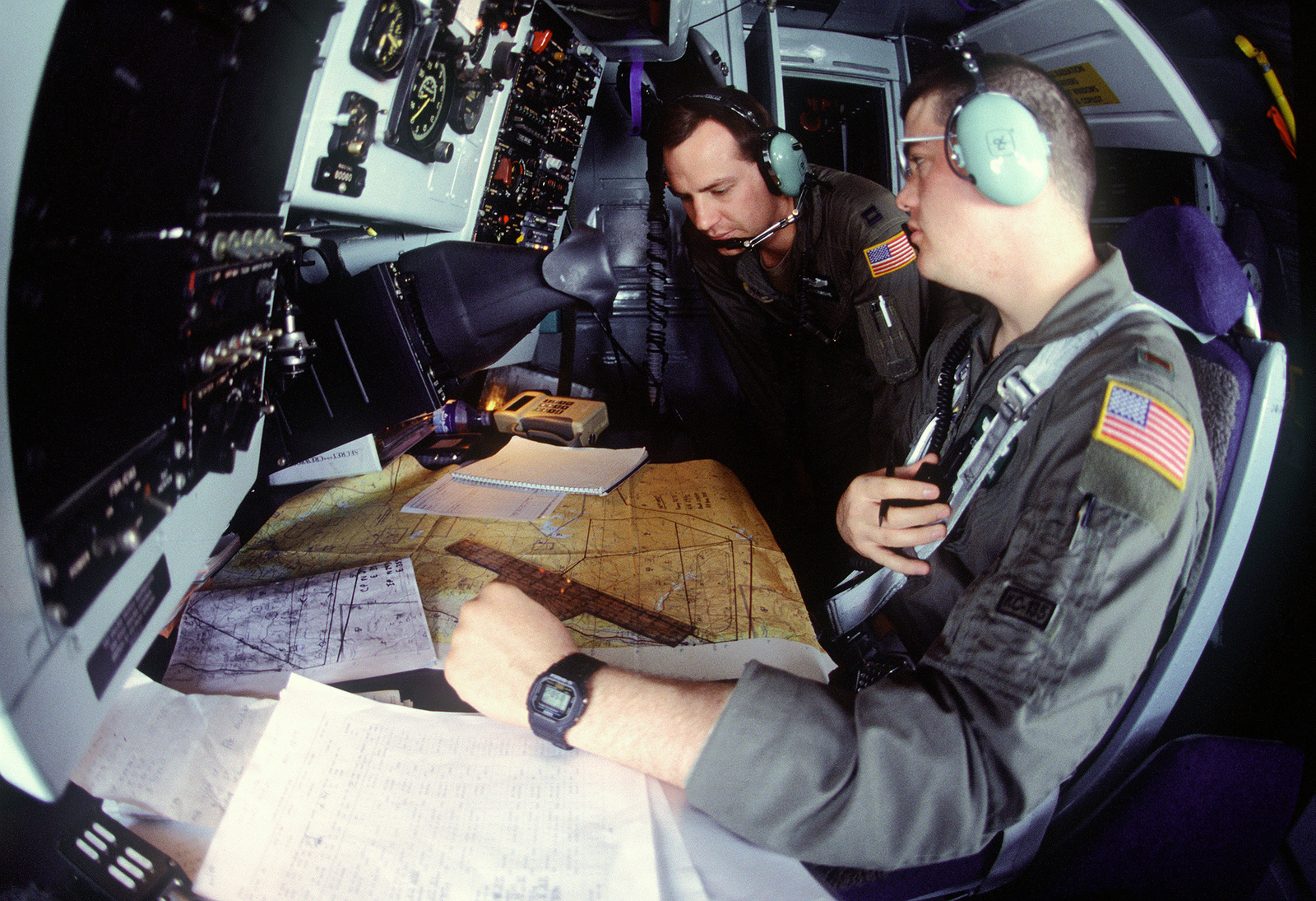 Navigators, 2nd Lieutenant Mathew C. Brennan (Right, Hometown: Baltimore, Maryland) and Captain Rod F. Cosgrove (Left, Hometown: Colorado Springs, Colorado) from the 96th Air Refueling Squadron, Fairchild Air Force Base, Washington check the navigation maps during a mission in a KC-135 aircraft over Jordan in support of the Air Power Expeditionary Force. An ancillary mission of the Force is to assist US Air Force and other multinational forces operating in Saudi Arabia and other nearby countries patrol the no-fly zone over southern Iraq
