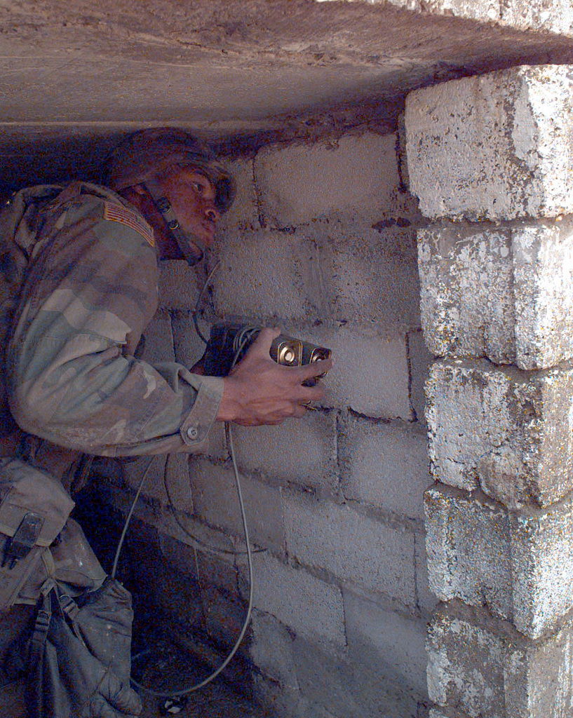 SPC Michael Wallace, Charlie Company, 23rd Engineers, Engineer Brigade, looks for a place to put a TNT charge in order to destroy this cement block Croatian bunker located near check point 130, (Grid 128849) Bosnia-Herzegovina during Operation Joint Endeavor