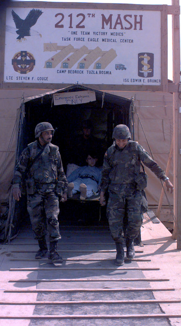 Members of the HHB 5-3 ADA Medical Battalion from McCulley Barracks Germany, carry a civilian patient on a litter back into the ambulance after being examined by a doctor from the 212th MASH Mobile Medical Support Battalion at Camp Bedrock, Bosnia-Herzegovina. The patient was involved in an automobile accident with a US IFOR( Implementation Force) vehicle during Operation Joint Endeavor