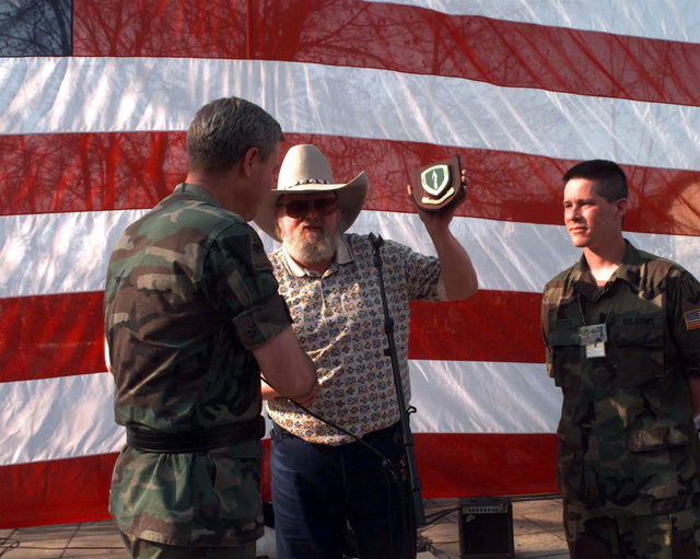 Country singer Charlie Daniels is presented with a plaque after his performance and autograph signing session at the Allied Command Europe Rapid Reaction Corps picnic during JOINT ENDEAVOR