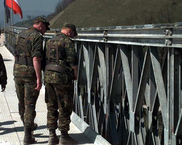 In the afternoon of the 21st of April, 1996, in the small town of Visoko, two German Army Engineers inspect the Sixty Ton Maximum Load Capacity Bridge, now the Visoko Bridge, while crossing it during the opening. The Visoko Bridge was built by German and Romanian Army Engineers during the months of March and April, 1996. Before the rebuilding of the bridge, the surrounding area had to be cleared of mines that were laid after its destruction. The old Visoko bridge was destroyed in the beginning of the confrontations between Bosnian Muslims and Bosnian Serbs