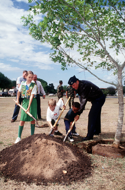 (Left to right) Lisa Lage, 11; of Girl Scout Troop 154; Colton Botson, 7; and Ray Cage, 7 assist COL. David Lopez, Vice Commander, 12th Flying Training Wing, plant a tree at the site of the future Youth Center. The tree was provided by the Free City U.S.A. Foundation