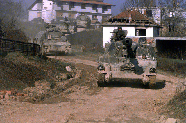 On the morning of April 22nd, 1996, soldiers of 1ST Platoon, A Battery, 4th Battalion, 29th Field Artillery Regiment, drive their M109-A2, 155mm Self Propelled Howitzers, and CAT-V (carrier, ammunition, tracked, vehicle), down a hill near the town of Donje Caparde (CQ 379 183), in the Zone of Separation, during a 2 gun Artillery raid in support of Operation Joint Endeavor