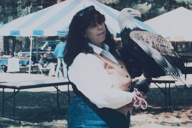 Jackie Fallon, a bird handler with the University of Minnesota Raptor Center, Pine View Recreational Area, displays a Bald Eagle for a crowd of observers attending Earth Day activities