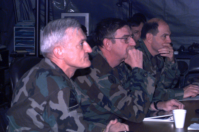 Major General Walter Yates, the Deputy Commander for USAREUR FWD (left), along with General William Hartzog, the TRADOC Commander(center), and the Deputy CHIEF of STAFF for Training, Major General Carl Ernst, sit in the tactical operations center on Taszar main to receive mission briefs and gain insight to US Operations in Hungary during Operation Joint Endeavor