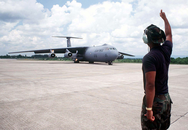 US Air Force STAFF Sergeant Guy Moore, 615th Air Mobility Maintenance Squadron, Travis Air Force Base, California, gives a thumbs-up as a C-141 Starlifter aircraft safely taxis to position at Hat Yai International Airport during Exercise COBRA GOLD '96