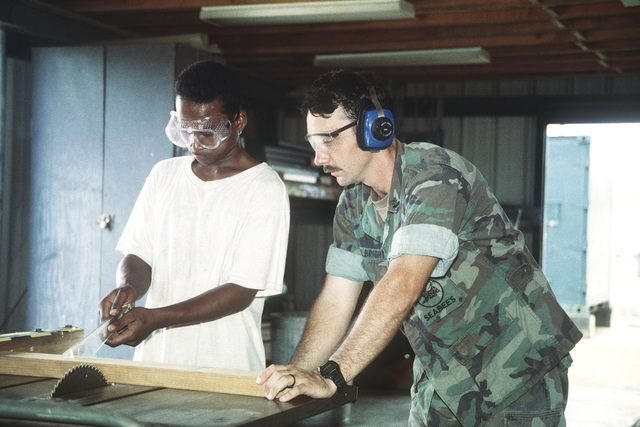 Equipment Operator Second Class (EO2) Larry Fulbright instructs a local worker of Palau in the basic functions of carpentry. After an apprenticeship of one year of training for the local work force, the Seabees hold an awards ceremony for the local residents who are then ready to join the local labor force