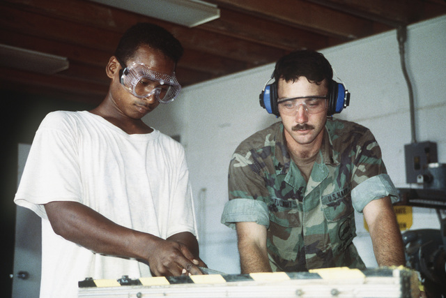 Equipment Operator Second Class (EO2) Larry Fulbright instructs one of several local workers in the basic functions of carpentry. The Seabees operate an apprenticeship program with the local labor force to aid in training for self-help programs