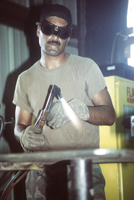 Steelworker Second Class (SW2) Frank Luevanos prepares to cut a piece of sheet metal in the welding shop of the Naval Mobil Construction Battalion Three (NMCB-3) Civic Action Team compound