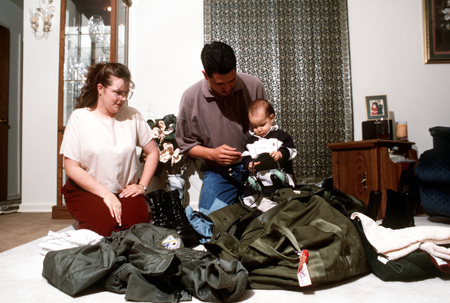 SENIOR AIRMAN Chris Kimber, 964th AACS, prepares for a deployment while his wife, SENIOR AIRMAN Michelle Kimber, USAF Hospital, and their son, Alexander, help pack the flight gear.(Published in AIRMAN Magazine May 1996 ) Exact Date Shot Unknown