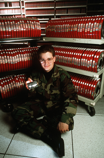 SENIOR AIRMAN Raymond Ivie, a computer operator with the 752nd Computer Systems Squadron, sits in front of a rack of 250 nine-track magnetic tapes that can be stored on the 8MM data cartridge he is holding. This data storage facility update to data cartridges supports the ever expanding mission of the E-3 Airborne Warning and Control System (AWACS) aircraft.(Published in AIRMAN Magazine May 1996 ) Exact Date Shot Unknown