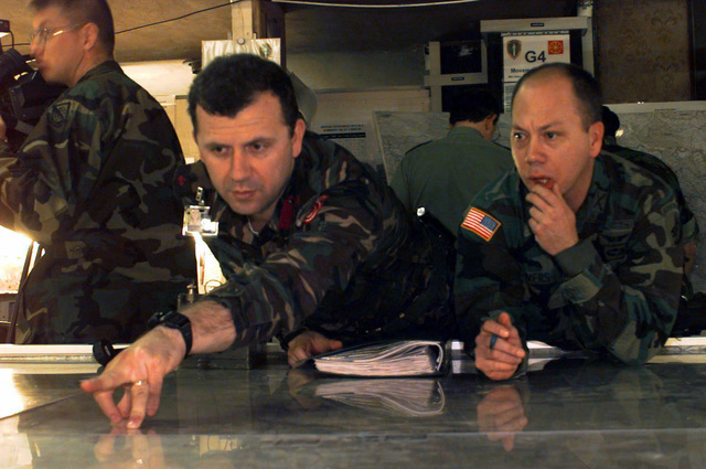 An unidentified US soldier and an unidentified foreign soldier look at a map covered with plastic. Both soldiers are involved in Operation Joint Endeavor. Operation Joint Endeavor is a peacekeeping effort by a multinational Implementation Force (IFOR), comprised of NATO and non-NATO military forces, deployed to Bosnia in support of the Dayton Peace Accords