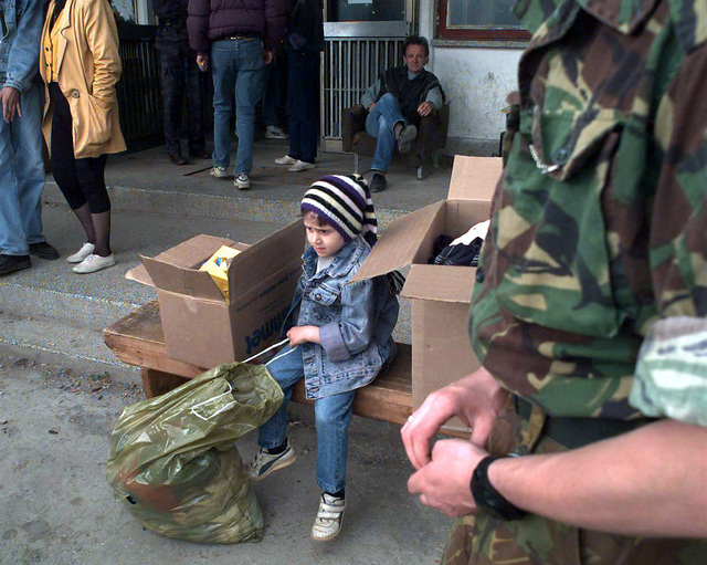 A Serbian refugee child, holding the drawstring of a large plastic bag that is half full of donated goods, sits between two box filled with donated clothes and books on a wooden bench. A Royal Army (British) soldier's torso in seen in the immediate foreground and other Serbian refugees are seen standing and stitting in the background around the child. The soldier is part of the Allied Command Europe Rapid Reaction Corps and is in Bosnia in support of Operation Joint Endeavor. Operation Joint Endeavor is a peacekeeping effort by a multinational Implementation Force (IFOR), comprised of NATO and non-NATO military forces, deployed to Bosnia in support of the Dayton Peace Accords