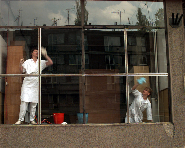 Looking in, from the outside, two men concentrate on cleaning the windows. The reconstruction, rebuilding and cleaning of Sarajevo, Bosnia has begun. Since the arrival of the Implementation Force in Bosnia, the residents of Sarajevo have worked very hard at turning their city back into the beautiful place it was before the war. Everywhere around the city people are seen cleaning, repairing and building. Small things such as cleaning windows have made a big difference in the appearance of Sarajevo