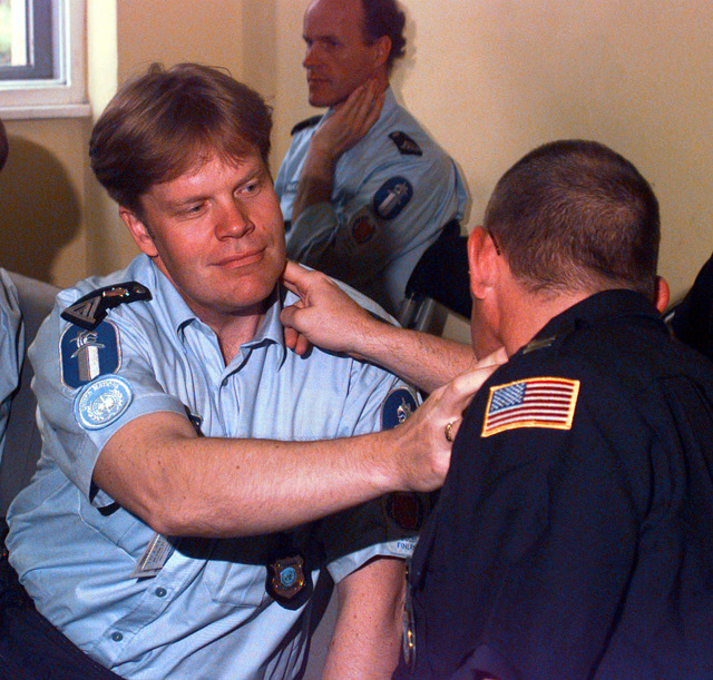 In a first-aid class, a Danish police officer and an American police officer practice on each other the proper procedure for checking a pulse on the neck during Operation Joint Endeavor