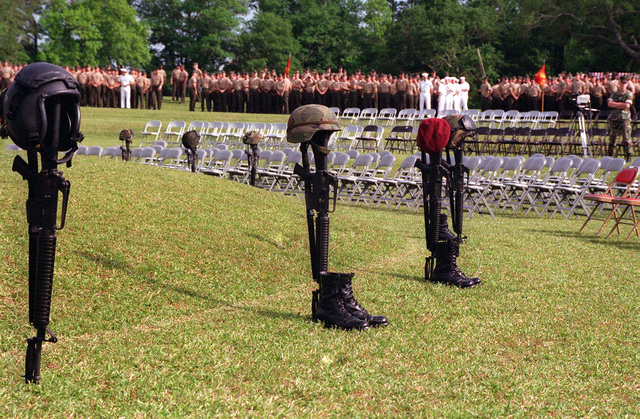Inverted M16A2 service rifles, serve as representation of the 14 service members who perished in the 10 May, 1996 helicopter accident at Camp Lejeune during CJTFEX 96. The different head gear on top of the rifles shows that helicopter pilots, crewman, infantryman, and a U.S. Army STAFF Sergeant, were among those who died. This photo was taken during the memorial service