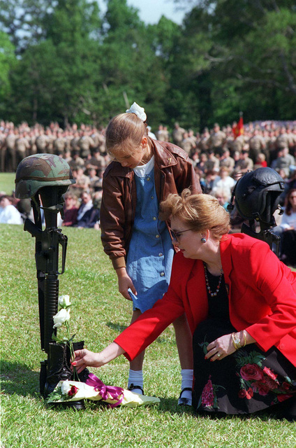 Megan Kusewski is joined by her aunt, Mary K. Evert, as they place flowers on the boots of Megans father, LT. COL. Michael D. Kuszewski, during a memorial service for the 14 service members who perished in a helicopter accident at Camp Lejeune on 10 May, 1996
