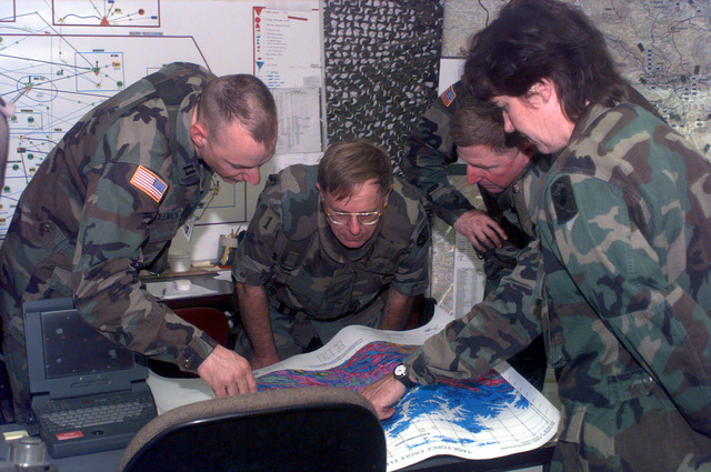 On the afternoon of 17 may 1996 Major General Charles G. Sutten, Commander Information System Command , looks at a map of the Node sites located in Bosnia-Herzegovina for Operation Joint Endeavor. Several officers share the map and assist with the briefing in the Tactical Operation Center of the 22d Signal Brigade