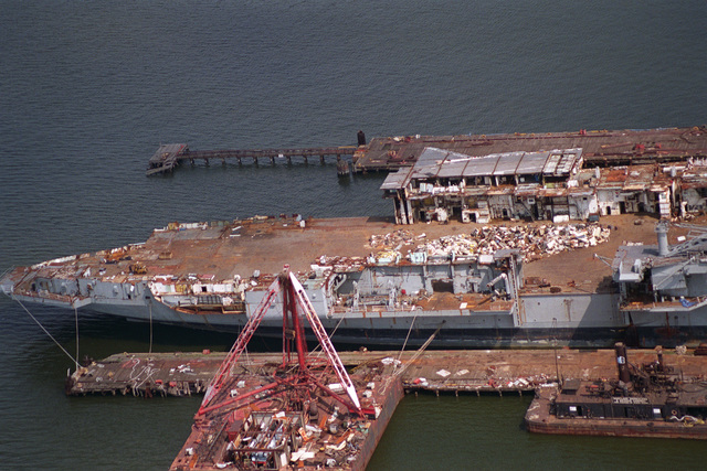 Aerial starboard side view of the decommissioned aircraft carrier CORAL SEA (CV-43) being scrapped out at the Seawitch Marine Salvage Company's Fairfield Terminal. The salvage company recently attempted to export the hulk to India to complete the scrapping operation, but a Federal court ruled against removing the ship from American waters as per the original contract on the sale of the vessel
