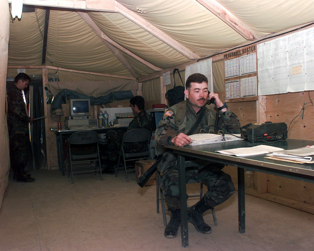 An officer talks on a field telephone in the Mayor's Office located in Steel Castle Base Camp in Bosnia. The Mayor's Office is responsible for all aspects of the base camp. Anything involving the base camp has to be approved by the Mayor during Operation Joint Endeavor