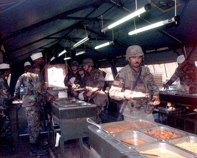 Four US military cooks stand at their stations inside the dining facility at Steel Castle Base Camp in Tuzla (East), Bosnia, serving and ready to servie food to four US Army troops. This dining facility is capable of feeding over 950 IFOR and DOD personnel per hour and personnel from the different units residing at Steel Castle Base Camp rotate cooking duties. The IFOR and DOD personnel in Bosnia involved in Operation Joint Endeavor. Operation Joint Endeavor is a peacekeeping effort by a multinational Implementation Force (IFOR), comprised of NATO and non-NATO military forces, deployed to Bosnia in support of the Dayton Peace Accords