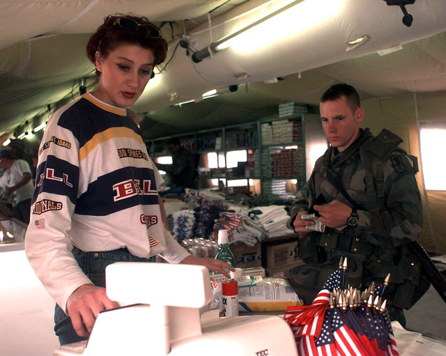 Ms. Radic Jelica, a local Bosnia woman hired by AAFES to work as a cashier at the Steel Castle Camp Post Exchange (PX) at Tuzla, rings up a purchase for 2LT Larry Doss, 17th Signal Battalion, attached to the 141st Signal Battalion out of Kitzingen, Germany. The PX is located inside a Deployable Rapid Assembly Shelter (DRASH) and supports IFOR and DOD personnel in Bosnia involved in Operation Joint Endeavor. Operation Joint Endeavor is a peacekeeping effort by a multinational Implementation Force (IFOR), comprised of NATO and non-NATO military forces, deployed to Bosnia in support of the Dayton Peace Accords