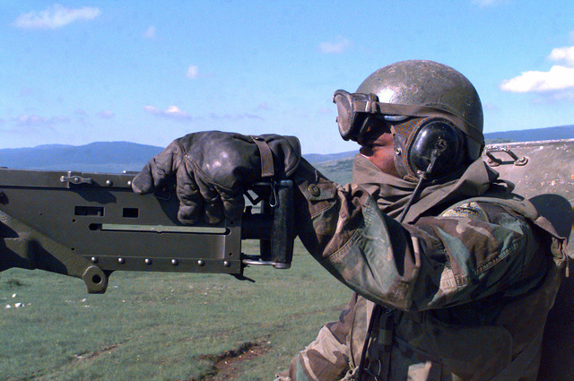 On the afternoon of May 23rd, 1996, SGT Terry Daniels, 1ST Platoon, B Battery, 4th Battalion, 29th Field Artillery, rides through the the top of an M-109A2, 155mm, Self Propelled Howitzer, and holds onto a 50 caliber machine gun, on the way to a live fire exercise near Glamoc, Bosnia-Herzegovina (XJ 5282), in support of Operation Joint Endeavor