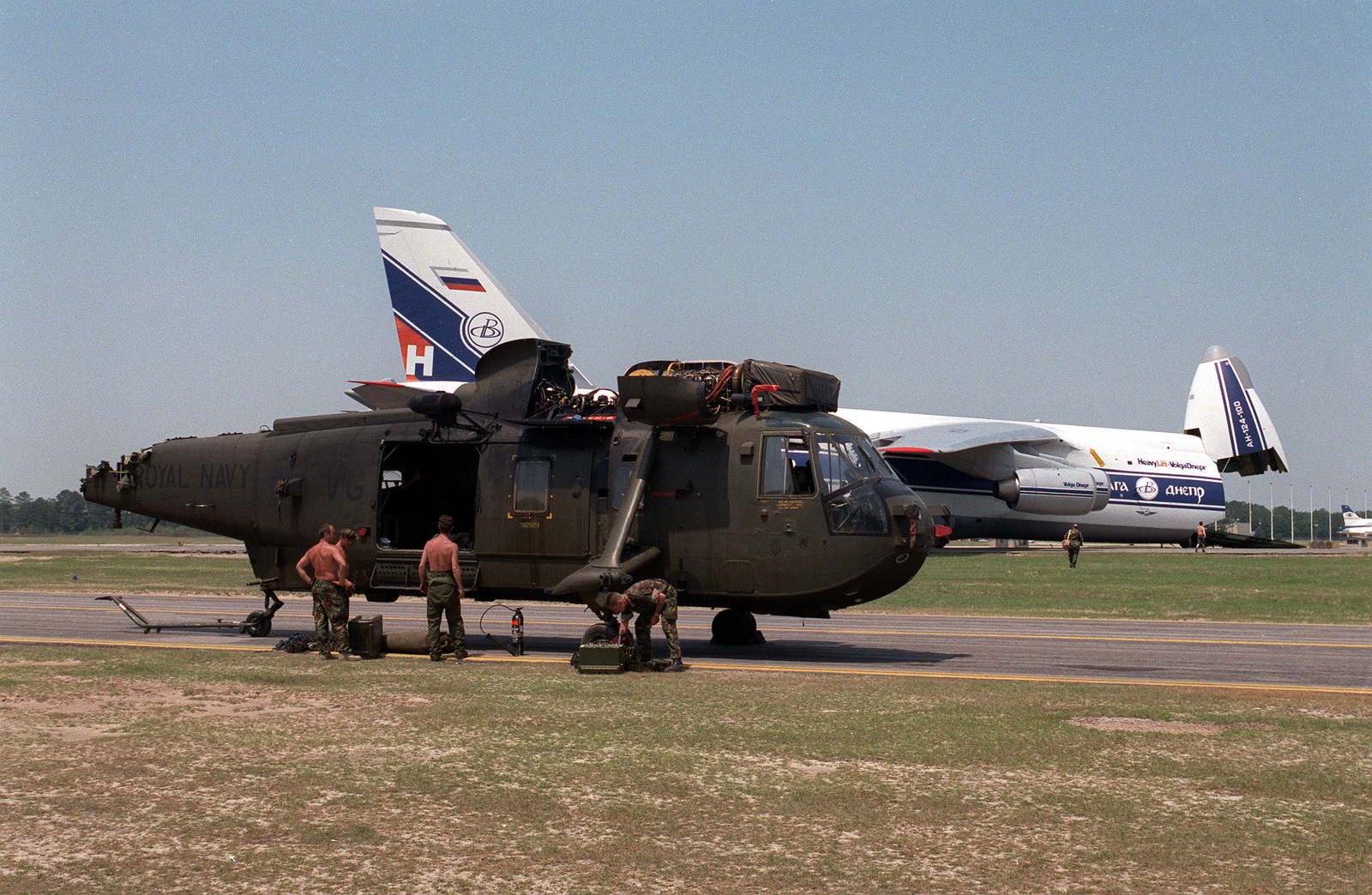 """Royal Navy and U.S. Army personnel work on a damaged Royal Navy Sea King Mk4 helicopter to prepare it for loading on the Russian Antonev AN-124-100 """"Ruslan"""" (NATO code name """"Condor"""") in the background. The Sea King sheared its tail rotor as a result of a hard landing on the Fort Bragg, N.C. reservation while participating in Exercise PURPLE STAR (Combined Joint Task Force 96 individual commands used their own code names for the exercise). The U.S. Army units used Exercise """"ROYAL DRAGON""""; U.S. Air Force units used Exercise """"BIG DROP III"""" as their code name, while the 17,000 British forces involved used Exercise """"PURPLE STAR."""""""