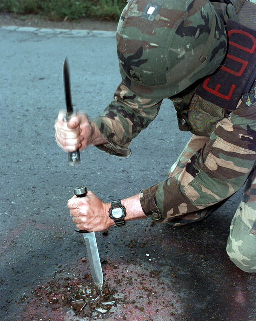 SSGT Richard Pierce, 55D, Explosive Ordinance Disposal SPECIALIST, 20th Explosive Ordinance Detachment, 596th Ordinance Battalion, Kaiserslautern, Germany, uses a pair of Diver's Knives to dig out a piece of UXO, a 120mm mortar round, embedded in Route New Jersey, YK 3571891164, while on a redeployment route reconnaissance mission during Operation Joint Endeavor