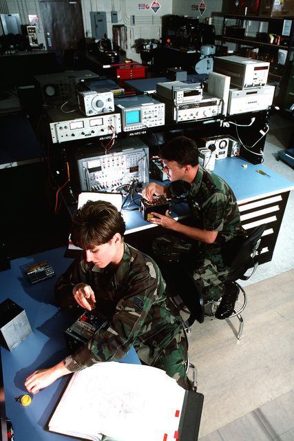 STAFF SGT. Karen Gantt (left), Communications Navigation Craftsman, adjusts a VHS receiver transmitter. SENIOR AIRMAN Brent Watkins, Guidance & Control Journeyman, aligns a UHF receiver transmitter. Both are assigned to the Avionics Element or the 741st Maintenance Squadron which supports the 1ST Rescue Group