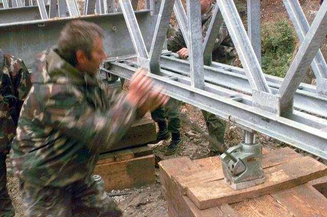 Several miles from the city of Sarajevo, Bosnia, a detachement of Hungarian Army Engineers finish assembling a Mabey Johnson 200 bridge before moving it into position during Operation JOINT ENDEAVOR. The bridge will allow easier vehicular traffic access throughout the surrounding area. Beginning in December, 1995, US and allied nations deployed peacekeeping forces to Bosnia in support of JOINT ENDEAVOR. Romania is one fourteen Partnership for Peace (PfP) countries that participated in the NATO lead peace mission that includes providing a safe environment