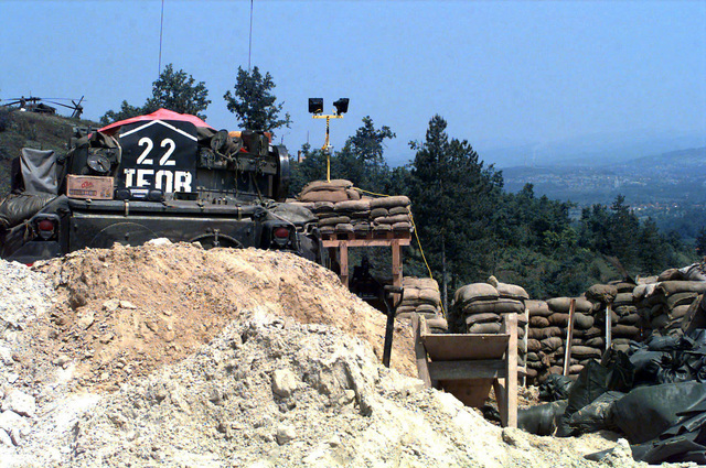 A sandbagged protected Observation Post located on remote signal Hill 425 in Bosnia - Herzegovina during Operation Joint Endeavor. In the immediate foreground, and partially blocking the observation post, is a large sand pile and right behind the sand pile is the rear view of a parked M3 Bradley Cavalry Fighting Vehicle. Operation Joint Endeavor is a peacekeeping effort by a multinational Implementation Force (IFOR), comprised of NATO and non-NATO military forces, deployed to Bosnia in support of the Dayton Peace Accords