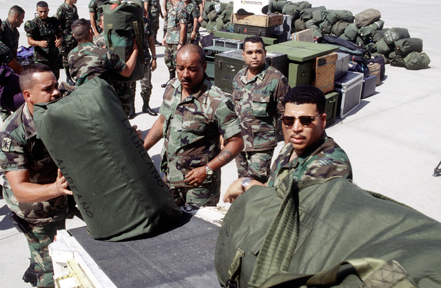Personnel from the 319th Transportation Team, Dover, Delaware, the 544th Military Police, Army National Guard, Yauco, Puerto Rico and the 125th Headquarters Detachment, Army National Guard, Ponce, Puerto Rico unload equipment and personal bags from the American Trans Air L-1011 that delivered the 544th and 125th to Biggs Army Airfield, El Paso, TX. These units are participating in Roving Sands '96, the largest annual US joint air defense training exercise