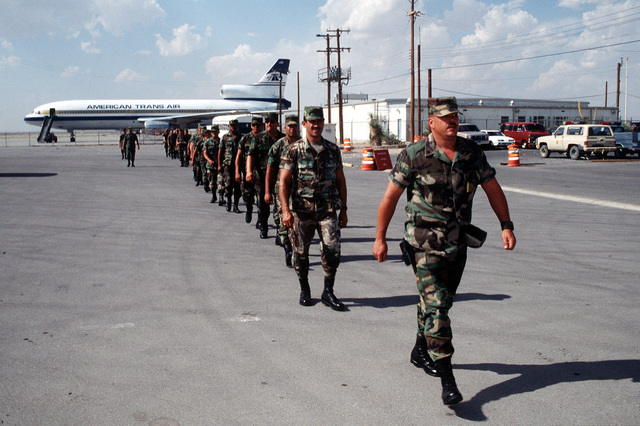 Personnel from the 544th Military Police, Army National Guard, Yauco, Puerto Rico and the 125th Headquarters Detachment Army National Guard, Ponce, Puerto Rico leave the flightline after unloading equipment and personal bags from the American Trans Air L-1011 that delivered their units to Biggs Army Airfield, El Paso, TX. These units are participating in Roving Sands '96, the largest annual US joint air defense training exercise