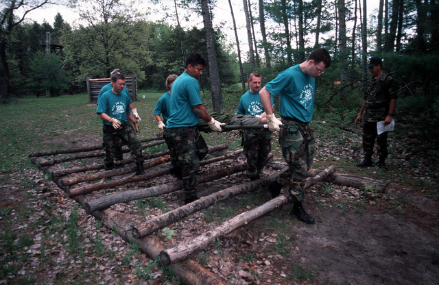 Members of Team Indiana, 181st Fighter Wing, Tere Haute, Ind., carry a stretcher through the obstacle course during the competition at Alpena Combat Readiness Training Center