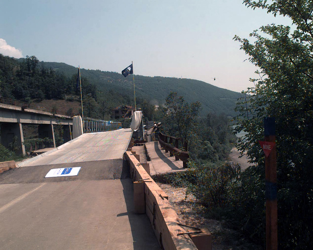 The Donji Bratinia Bridge, just north of the city of Gorazde, is re-opened after having been shut down after its' destruction by North Atlantic Treaty Organization air strikes. The new bridge is a British Mabey Johnson bridge assembled by a Battallion of German Engineers belonging and supporting the Implementation Force (IFOR) in Bosnia as part of Operation JOINT ENDEAVOR. Beginning in December, 1995, US and allied nations deployed peacekeeping forces to Bosnia in support of JOINT ENDEAVOR. The provision of a secure environment is at the heart of the reconstruction effort in Bosnia