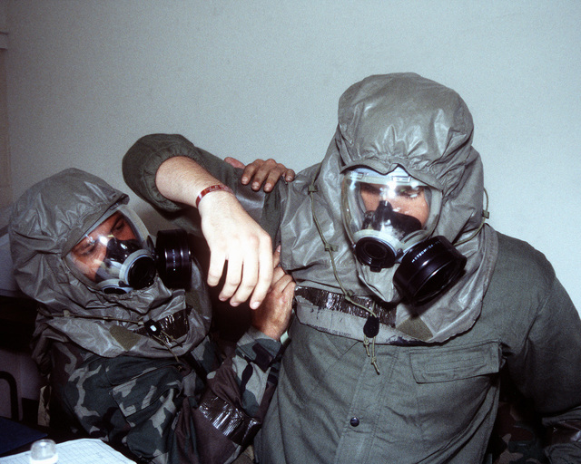 """Using the """"buddy system"""" participants at the Combat Readiness Training Center (CRTC), put on their chemical warfare gear during a simulated chemical attack at the CRTC. Top Dollar is an annual competition for Finance personnel. They compete as teams, that must learn to operate in a simulated hostile environment and participate in self-aid buddy care, chemical warfare, hostile forces, obstacle course and firing range exercises"""