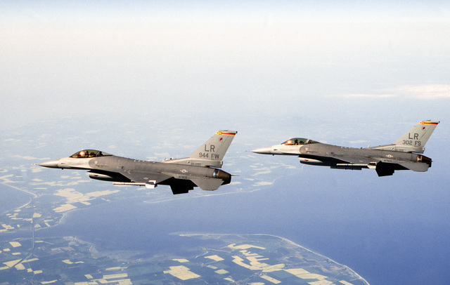 Air to air view of two Air Force Reserve F-16 Fighting Falcons flying over the coast of Denmark. The lead F-16 is the flag ship of the 944th Fighter Wing and the wing aircraft is the flag ship of the 302nd Fighter Squadron, both deployed from Luke Air Force Base, Arizona