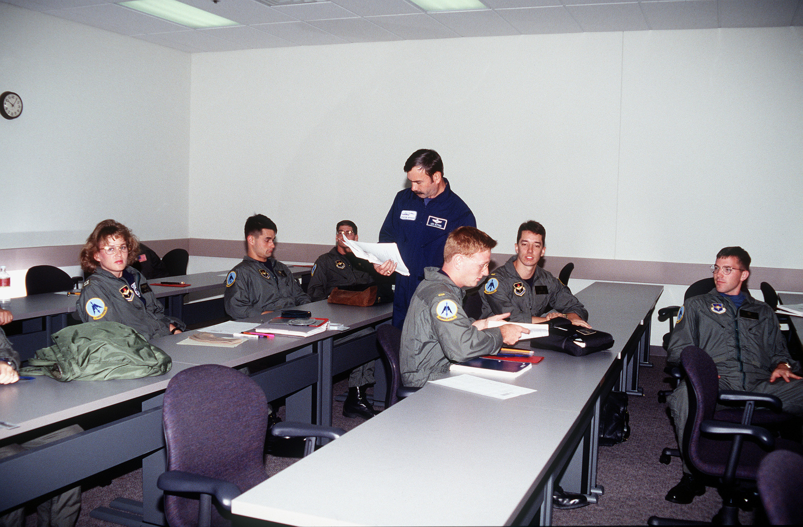 In the first combined U.S. Navy and U.S. Air Force joint navigator class of its kind, Instructor Les Sutton hands out graded tests in air navigation to students of class 9701 in Bldg. 743