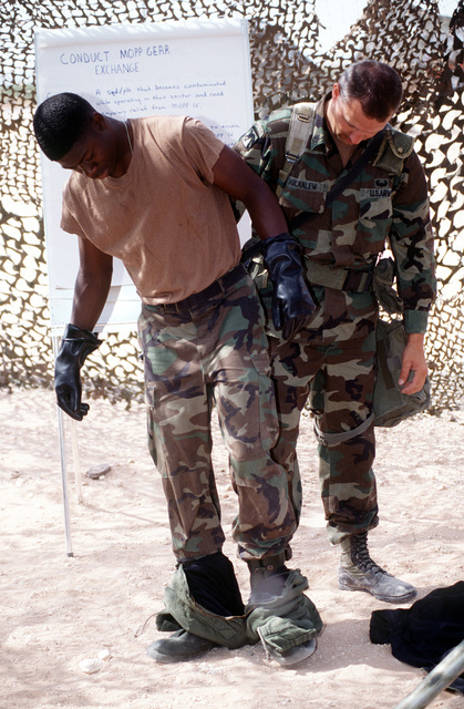 Chemical Warfare instructor STAFF SGT. Kevin Buckalew, 16th Signal Battalion, Fort Hood, Texas, helps remove a protective chemical suit from Private Shawn Harris, a 31st Romeo radio operator with the 16th Signal Battalion. The training was part of Roving Sands '96, the US military's largest annual joint air defense training exercise